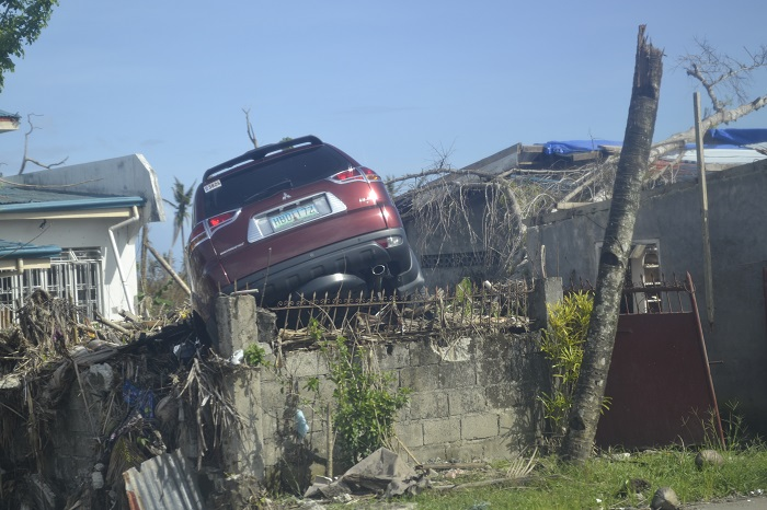 Typhoon devestation showing car above wall photo